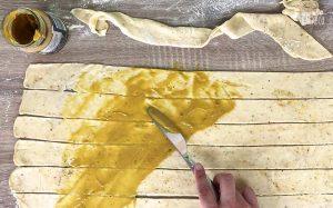 Herzhafte Brotrosen Rezept: Teigstreifen mit Senf bestreichen